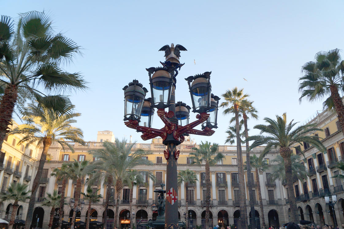 Hema_pose_ses_valises_barcelone_cityguide_placa_reial_lampadaire