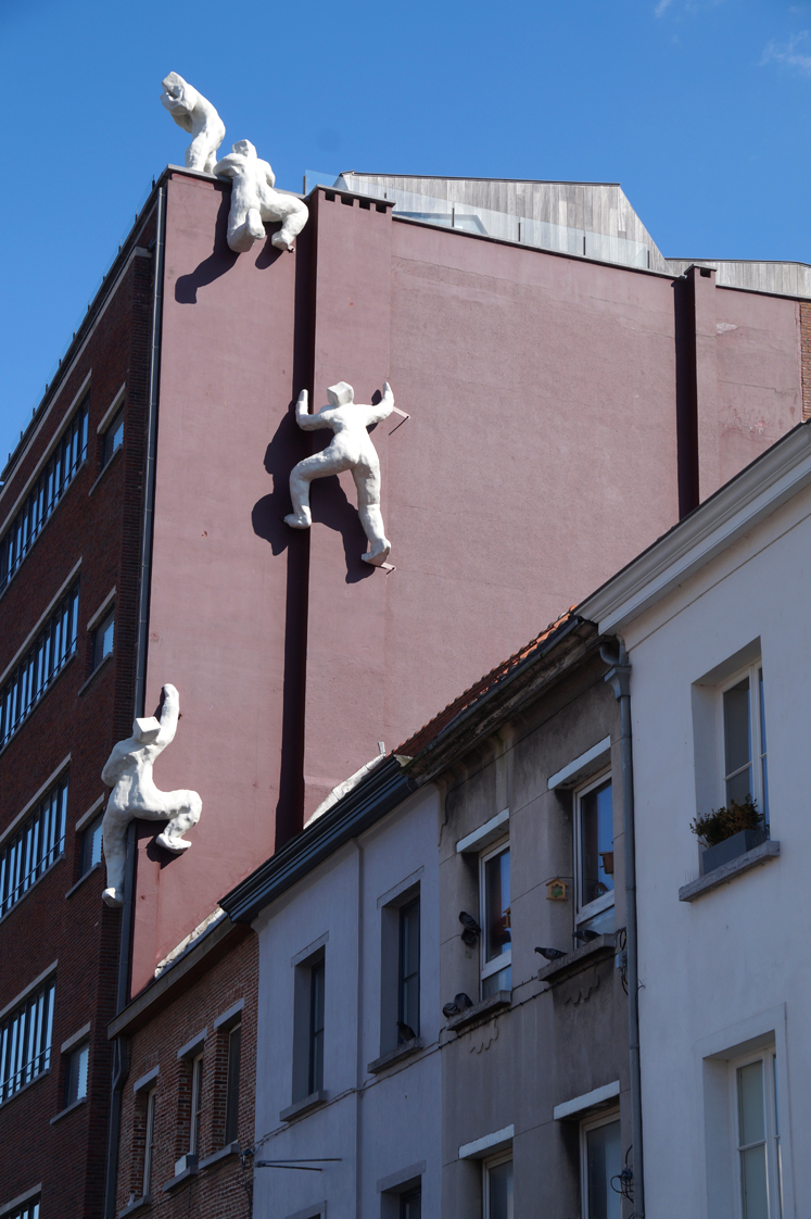 Hema_pose_ses_valises_anvers_sculpture_mur_escalade_homme